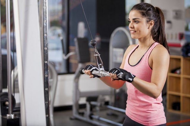Young woman using a pulley at the gym