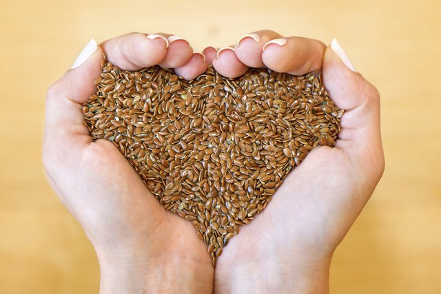 Two hands holding flaxseeds in the shape of a heart.