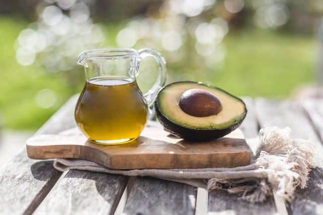A jug of avocado oil and half an avocado on a wooden table.