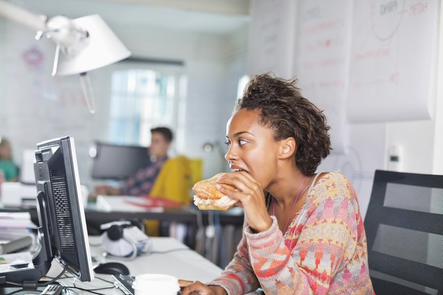 Woman eating whole grain bread (a complex carbohydrate) at work.
