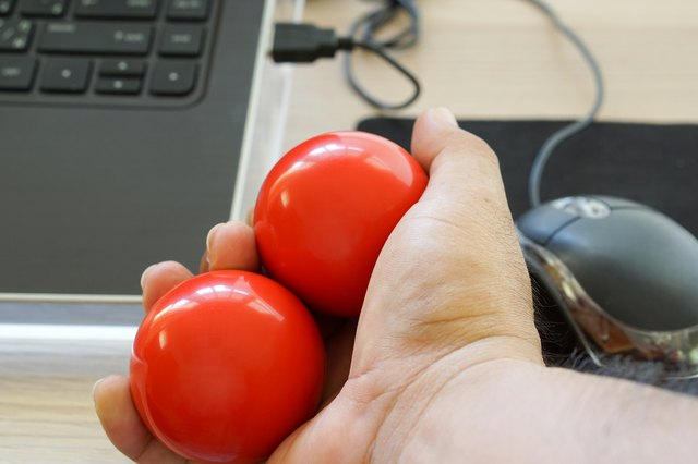 A hand at a desk holds two balls