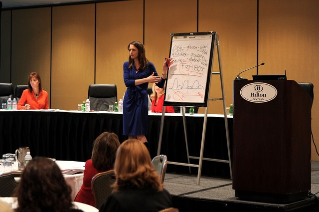 A nutritionist teaches a group about healthy food choices at a conference.
