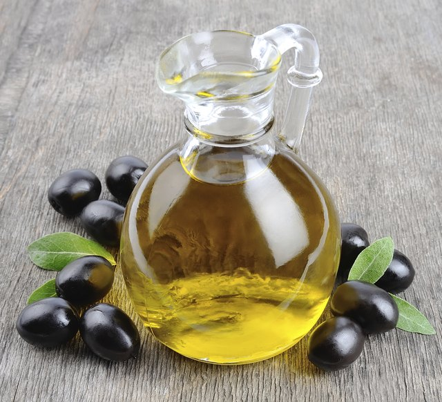 A small bottle of olive oil surrounded by olives