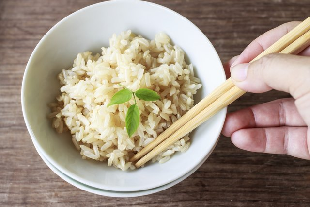 Someone about to eat steamed brown rice.