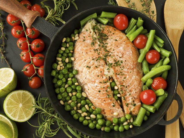 Salmon in a skillet with peas, pinenuts, green beans, and cherry tomatoes.