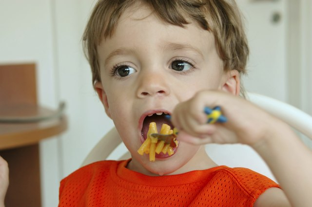 Toddler eating macaroni and cheeese