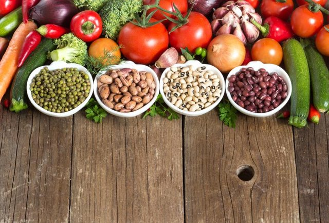 Legumes in bowls and vegetables on a wooden table