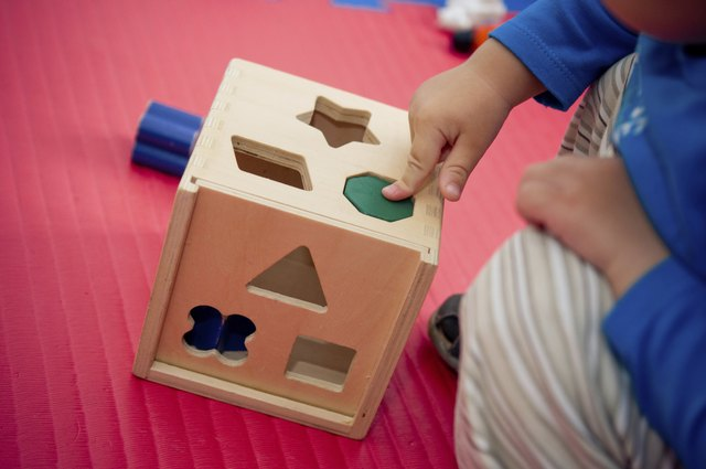 A child pushes a wooden block through a hole in a box.