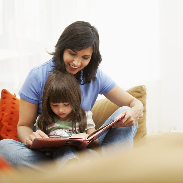 Child sitting in mother's lap reading book