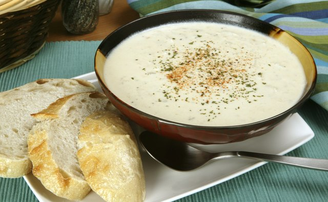 Bowl of New England clam chowder with sliced bread