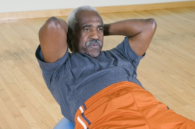 A man does sit-ups on a ball at the gym.