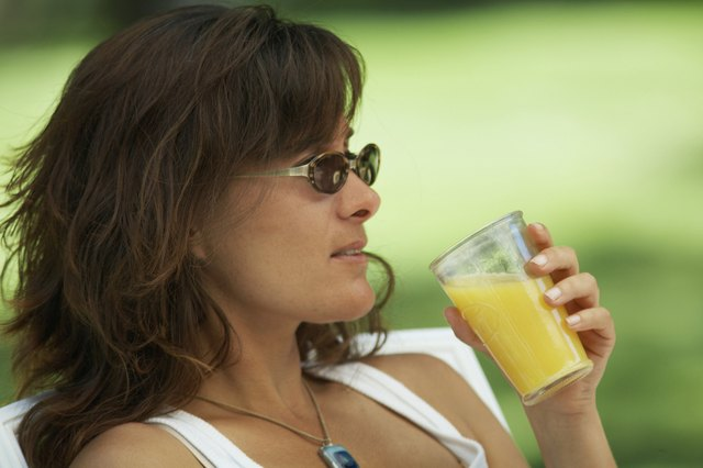 A woman reclines in a chair and drinks pineapple juice.