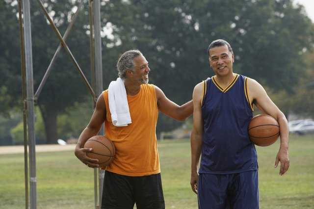 Two men talking after playing basketball