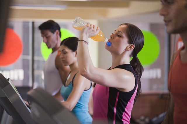 woman drinking sports drink in gym