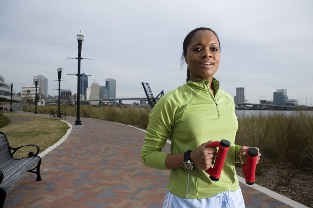 A woman jogging with weights in an urban park.