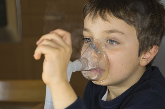 Young boy using a nebulizer for albuterol mist treatment