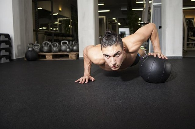 Roll the ball back and forth between push-ups to increase the difficulty.
