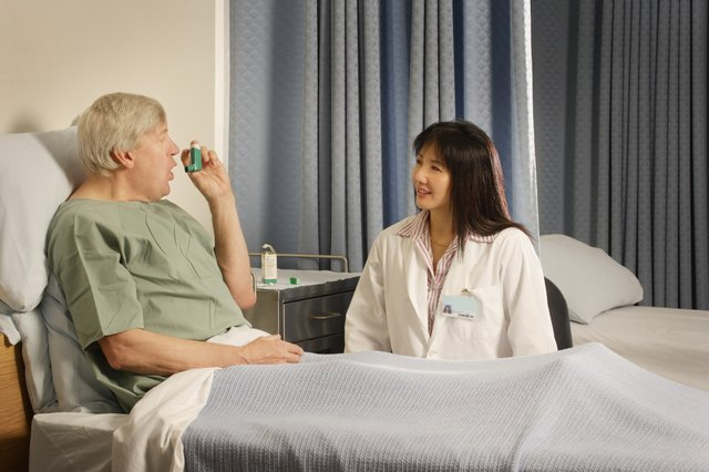 A female doctor teaches a senior male patient how to use an inhaler in a hospital room.