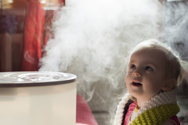 Little girl admires mist coming from humidifier