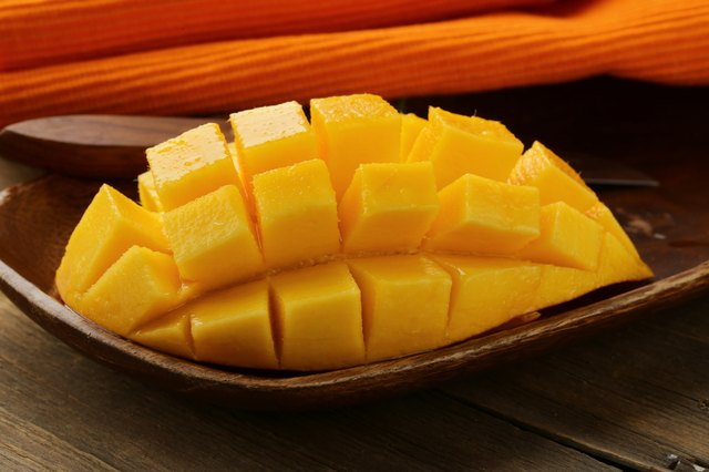 Fresh mango on a wooden plate