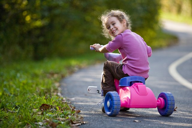 A little girl rides a tricycle on a path in the park in summer.