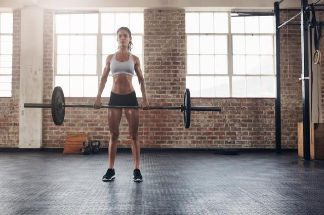 Perform deadlifts with a barbell or dumbbells at the gym.
