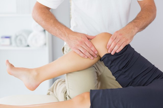 A physical therapist works on a patient's knee