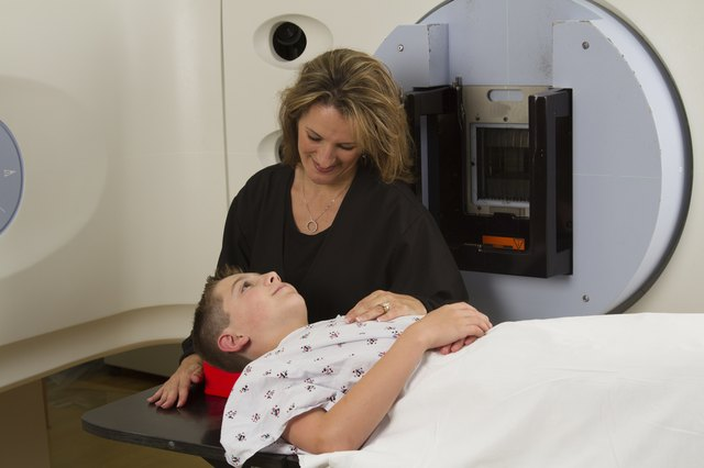 A female radiotherapy technican prepares a young cancer patient for radiation treatment