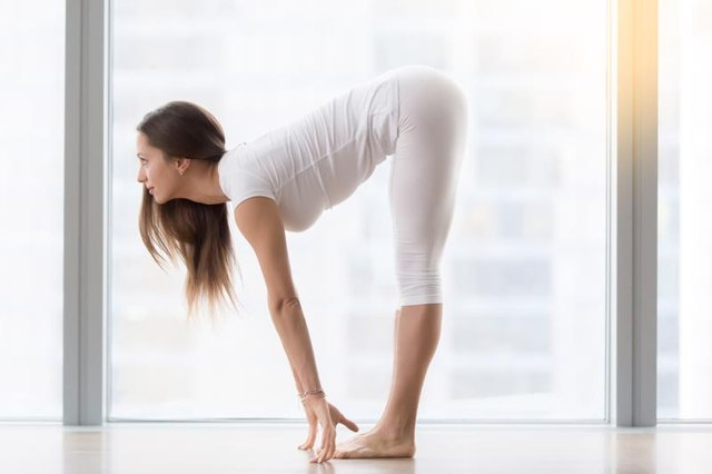 The halfway lift in Padahastasana helps your spine lengthen.