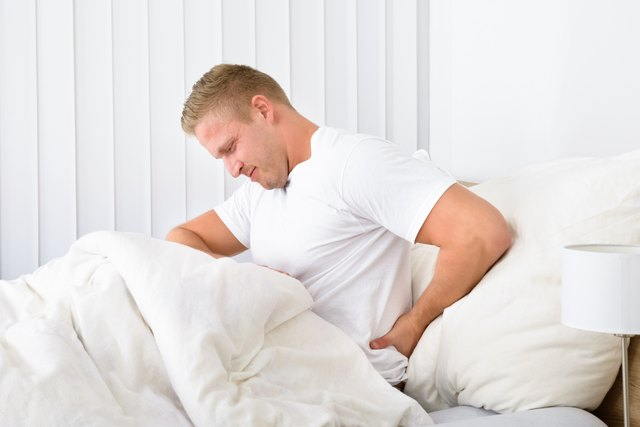 Man sitting up in bed holding his hip