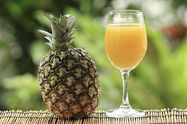 A goblet of pineapple juice stands next to an upright pineapple.