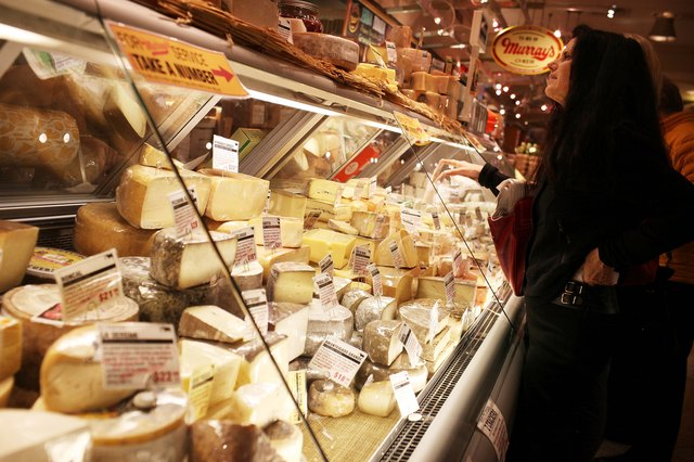 Woman at cheese display at deli counter