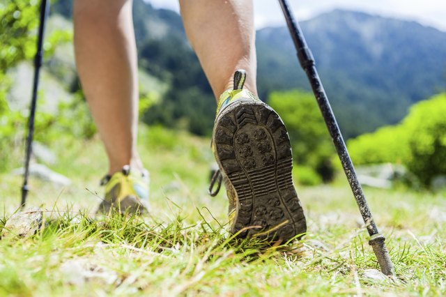 Woman's feet hiking in hills with walking poles