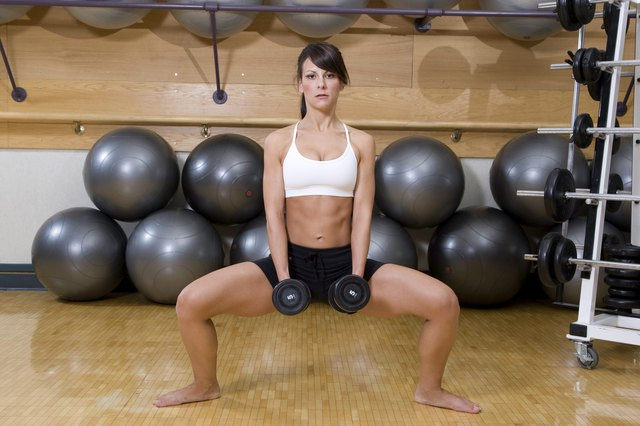 A woman doing squats in a gym