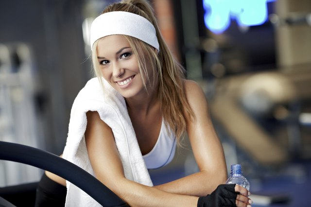 woman finishing up at gym with towel on shoulder