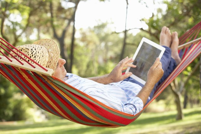 A man relaxes in a hammock and reads an ebook.