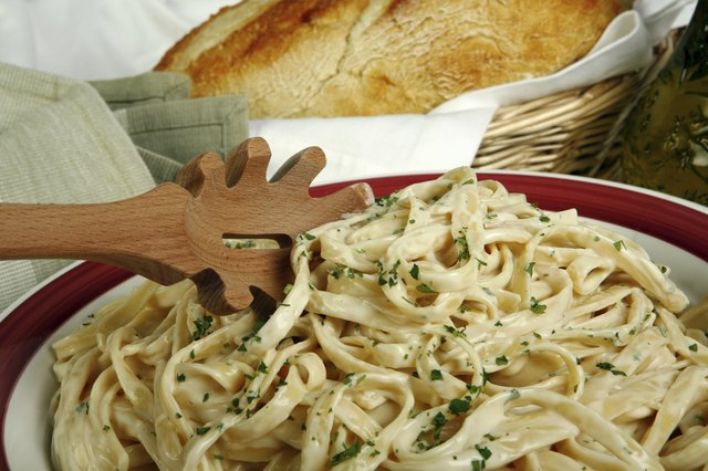 A close-up of a pasta dish served with bread.