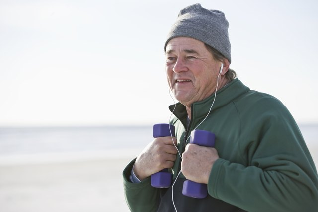 A man exercises with hand weights on a chilly day at the beach.