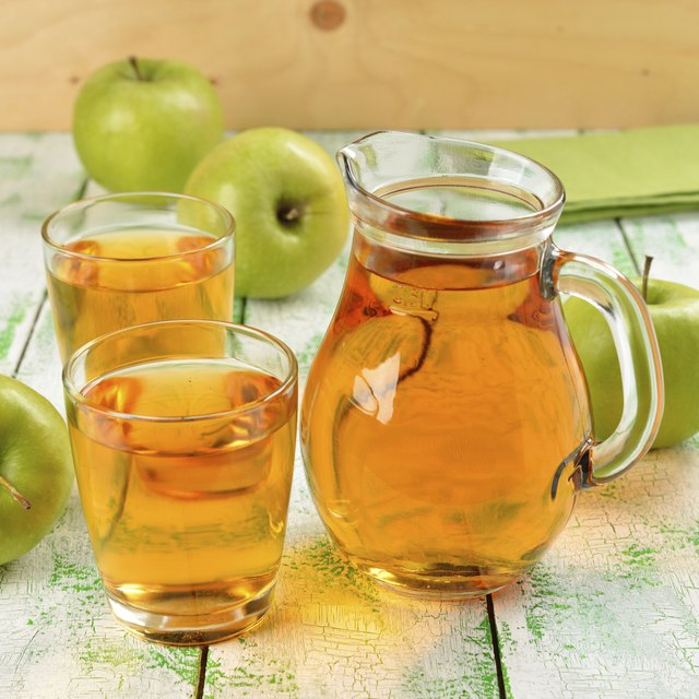 Pitcher and cups filled with apple juice