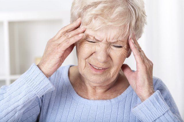 Senior woman with a migraine clutching her head