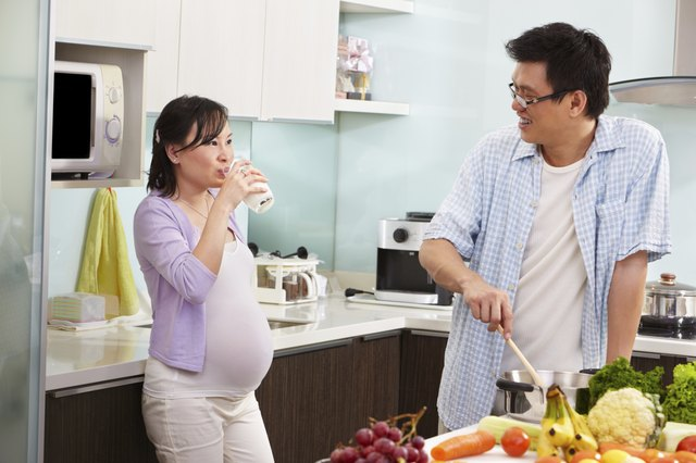 pregnant woman in kitchen with husband