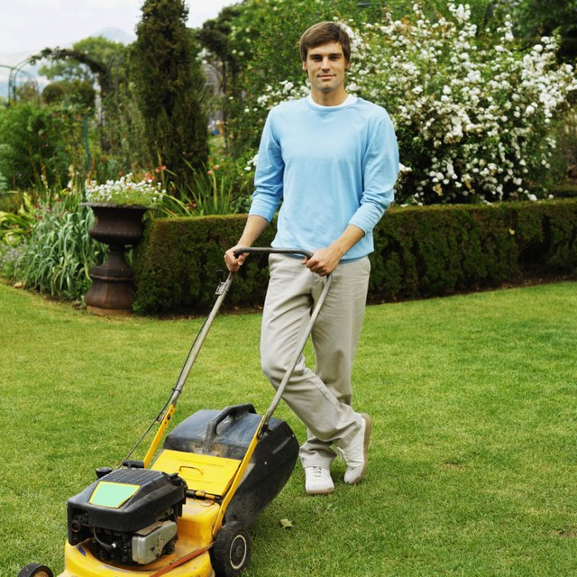 Young man mowing lawn with power mower.