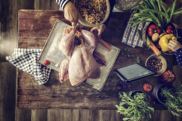Rub the raw turkey inside and out with seasonings, such as parsley, rosemary, rubbed sage, lemon pepper and salt.