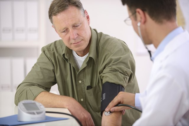Doctor checking a man's blood pressure