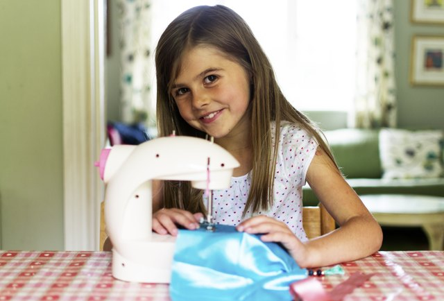 Young girl using a sewing machine