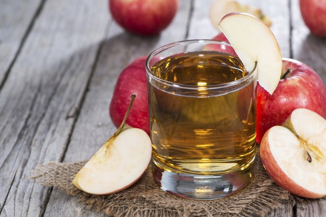 A glass of apple juice surrounded by slices of apples.