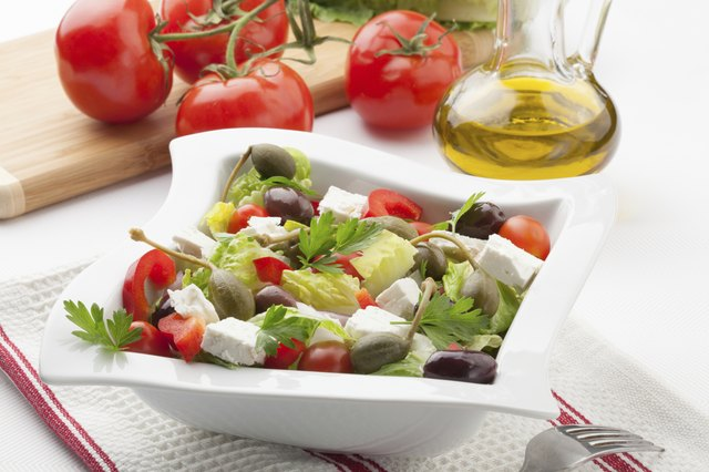A greek salad drizzled lightly with olive oil.