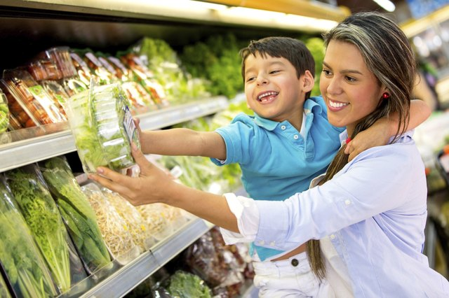 woman picking out vegetables with son