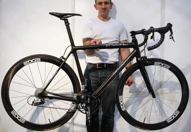 Man holding lightweight road bike with one finger