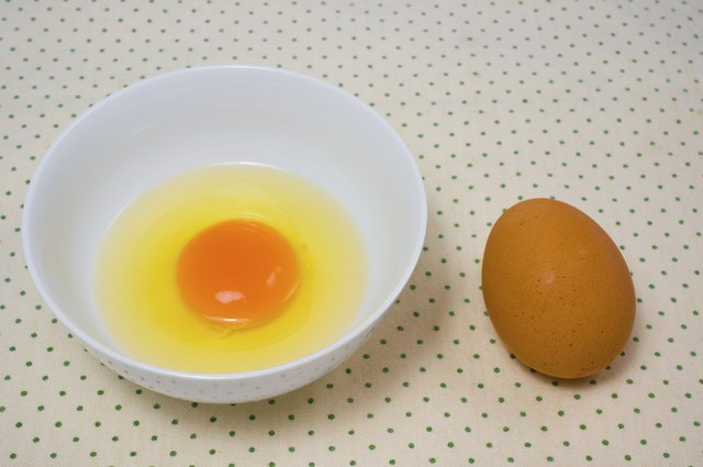 An egg yolk in a bowl next to a whole brown egg.